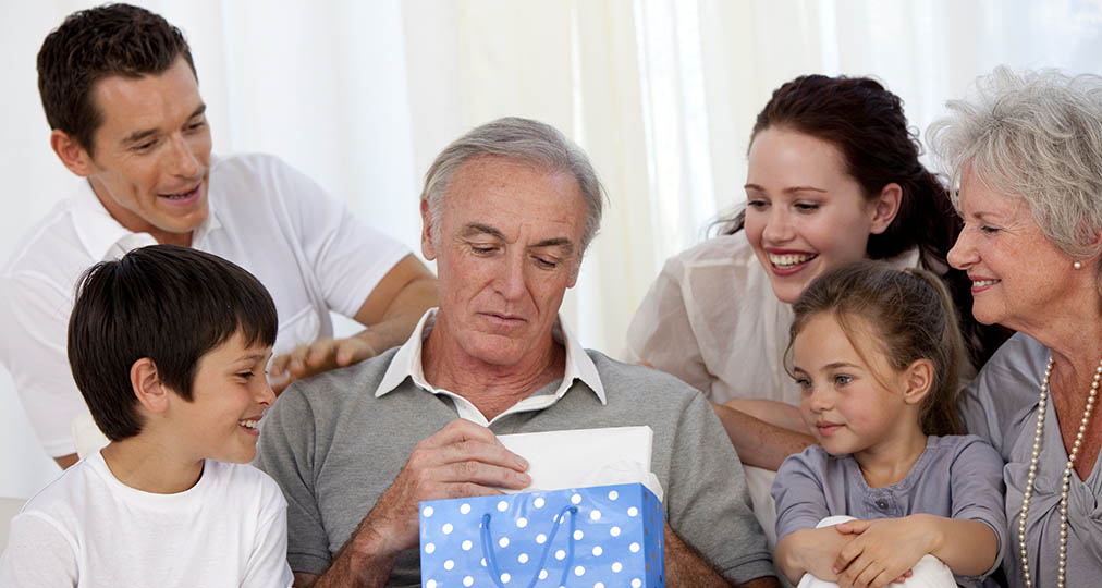 family together gifting the grandfather