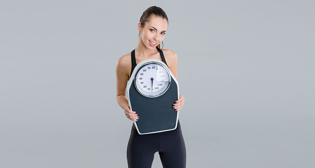 fitness girl holding a weight scale