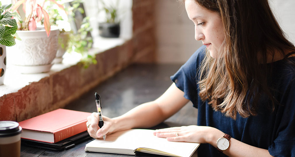 girl writing by hand in her notebook
