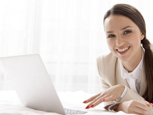 happy businesswoman with laptop in bed