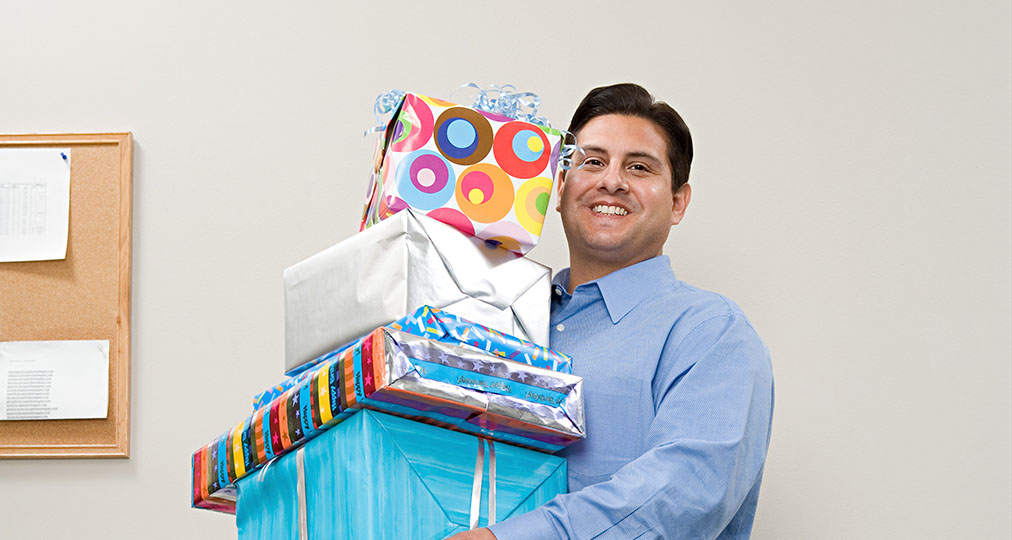 happy man holding lot of gift boxes