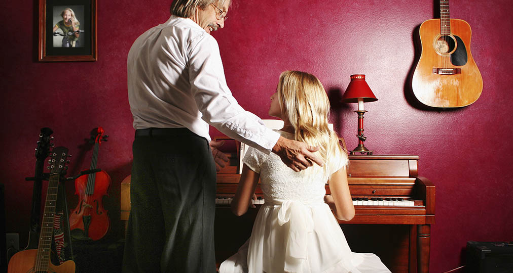 man and young woman near piano