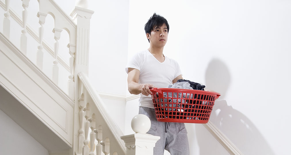 man carrying a basket with clothes