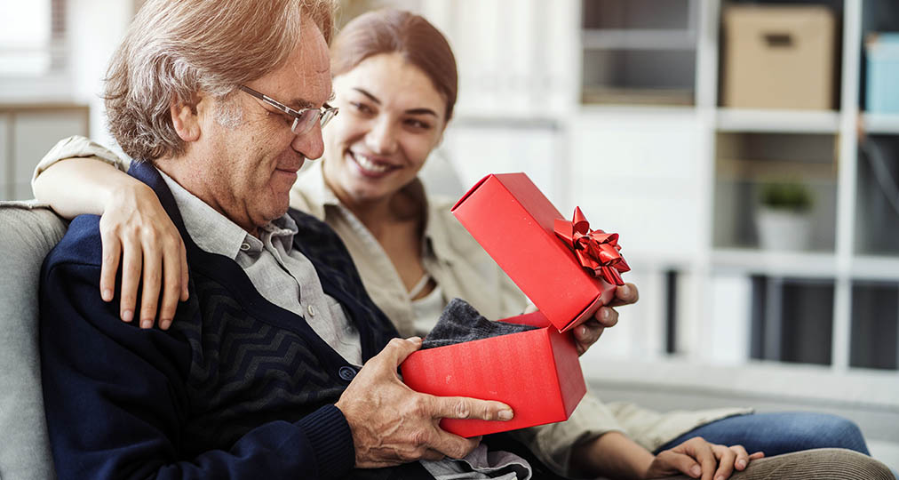 man receiving a gift from his daughter