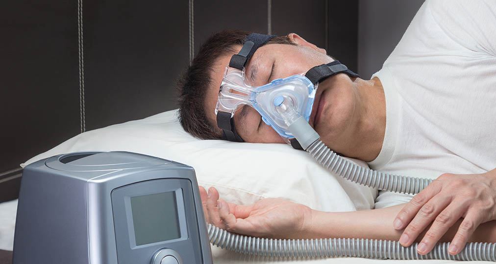 man sleeping wearing cpap machine