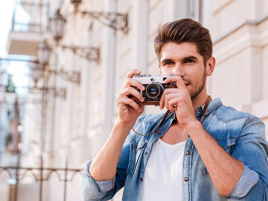 man taking photos with compact camera