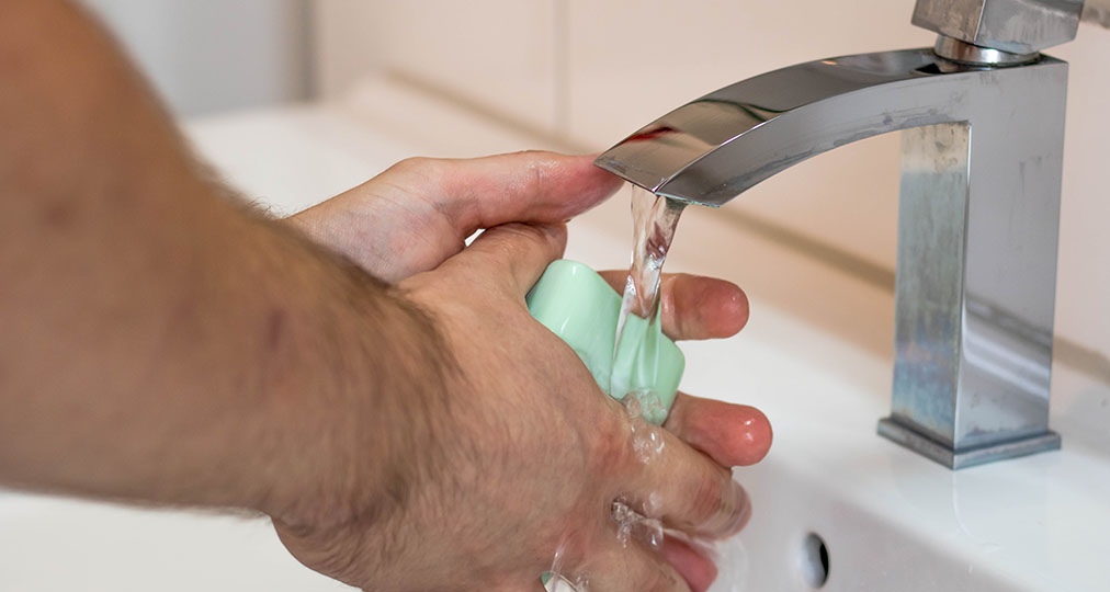 man washing his hands with water and soap