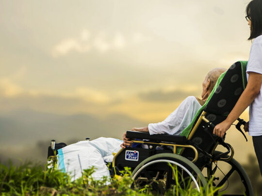 old man in wheelchair and caregiver