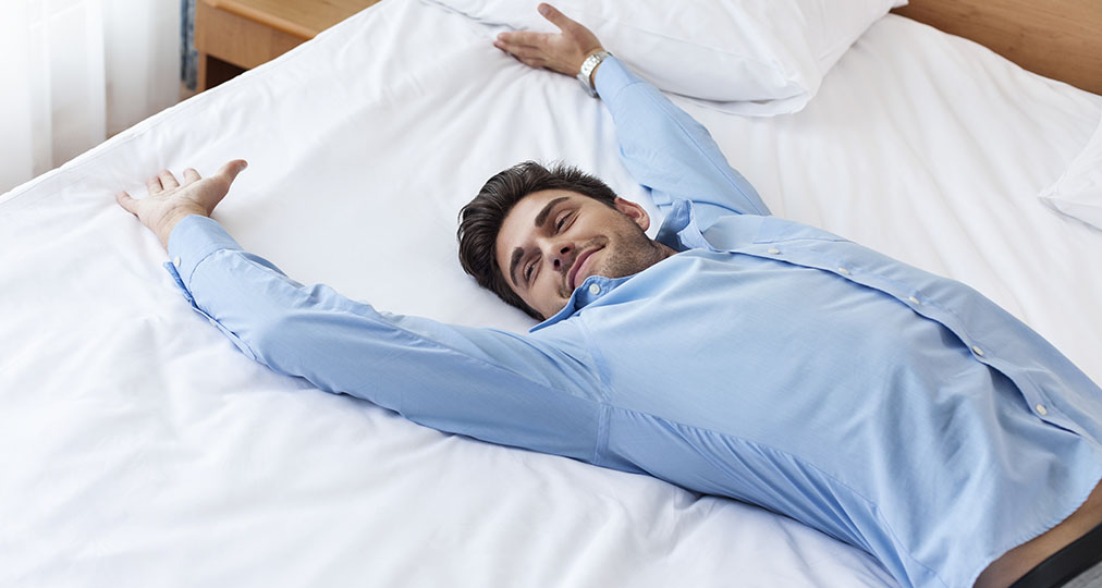 smiling man in hotel bed