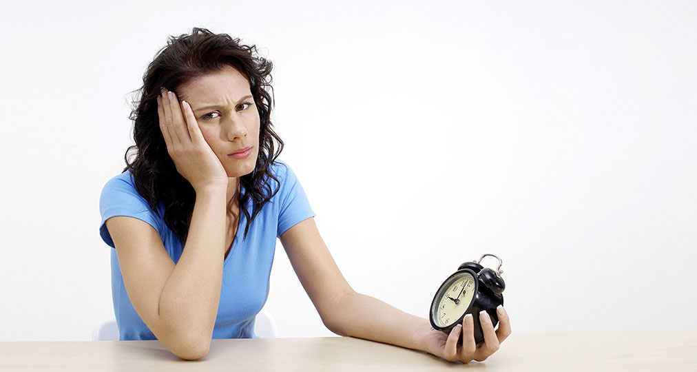 tired woman holding a clock