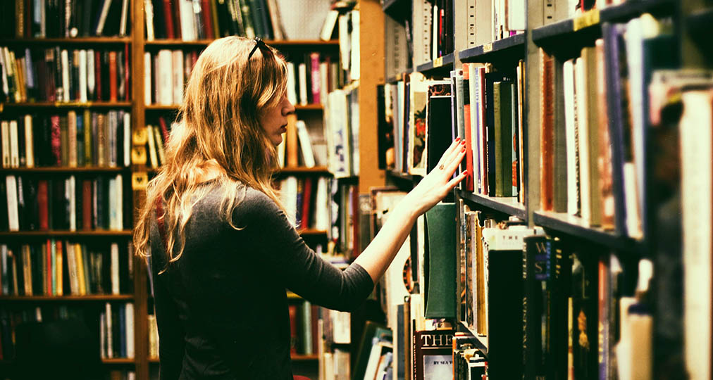woman looking for a book in the library
