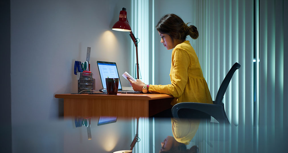 young woman reading while sitting at desk