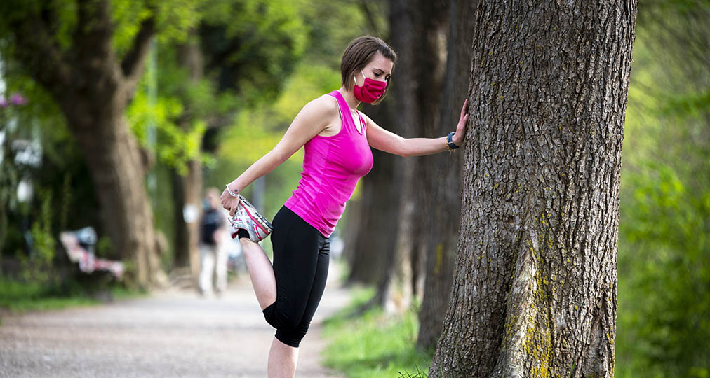 young woman stretching-in park wearing face mask