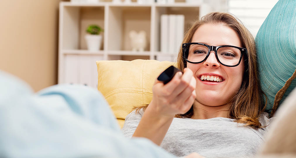 young woman using tv remote control